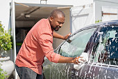 istock Mature black man washing car 1153409109