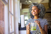 A beautiful black woman with white curly hair  drinks coffee in her kitchen