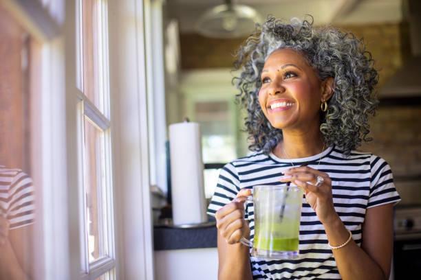 Reife schwarze Frau, die einen grünen Smoothie trinken – Foto