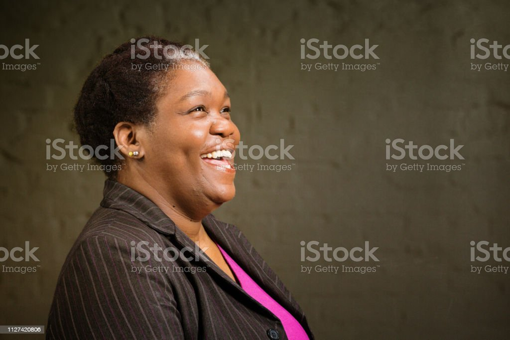 Mature black woman in her 50s laughing studio portrait with wall...