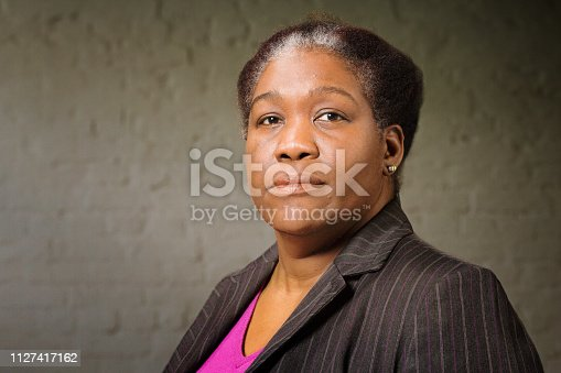 Mature black woman in her 50s studio portrait with wall background. She is dressed in a striped suit.