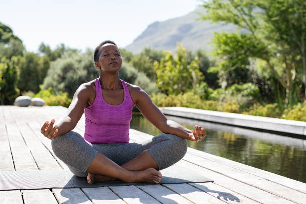 Mature black woman in lotus position Mature african woman practicing yoga and meditates in lotus position near swimming pool outdoor. Fitness black lady sitting in lotus pose with closed eyes. African american woman meditating at poolside with copy space. meditating stock pictures, royalty-free photos & images