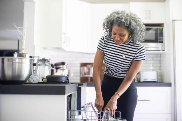 Reife schwarze Frau lodert Geschirrspüler – Foto