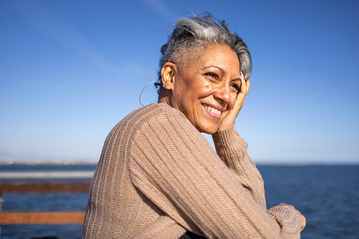 A mature black woman relaxes on the pier at the beach.
