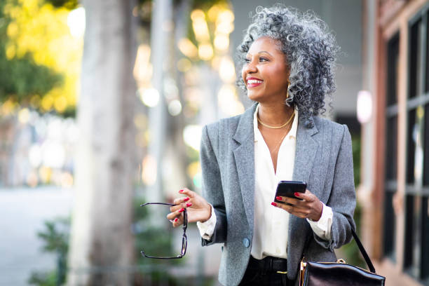 Mature Black Woman Texting While Walking in City An attractive black businesswoman on the town one mature woman only stock pictures, royalty-free photos & images