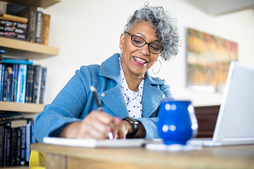A beautiful mature black woman with gray hair working from home.