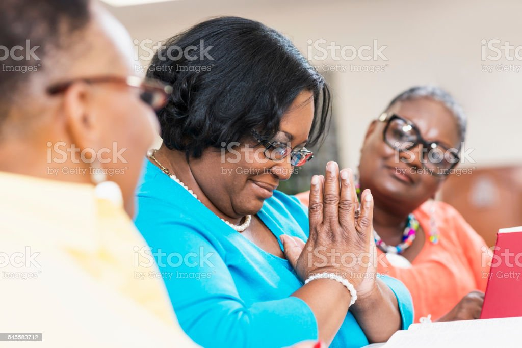 Mature black women with friends praying in bible study stock photo