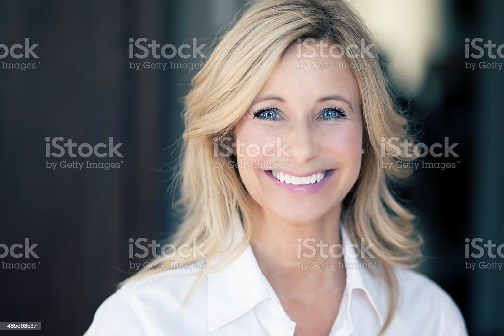 Mature blond woman smiles at camera stock photo