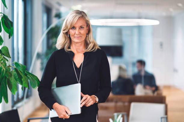 Mature blonde businesswoman holding a laptop stock photo