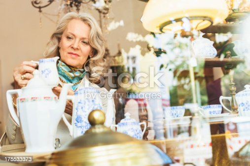Mature woman finding a cup in an antique store in Berlin, Germany. Shot through window.