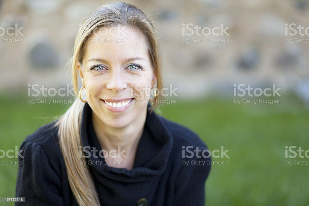 Mature blonde woman smiling at the camera outside stock photo