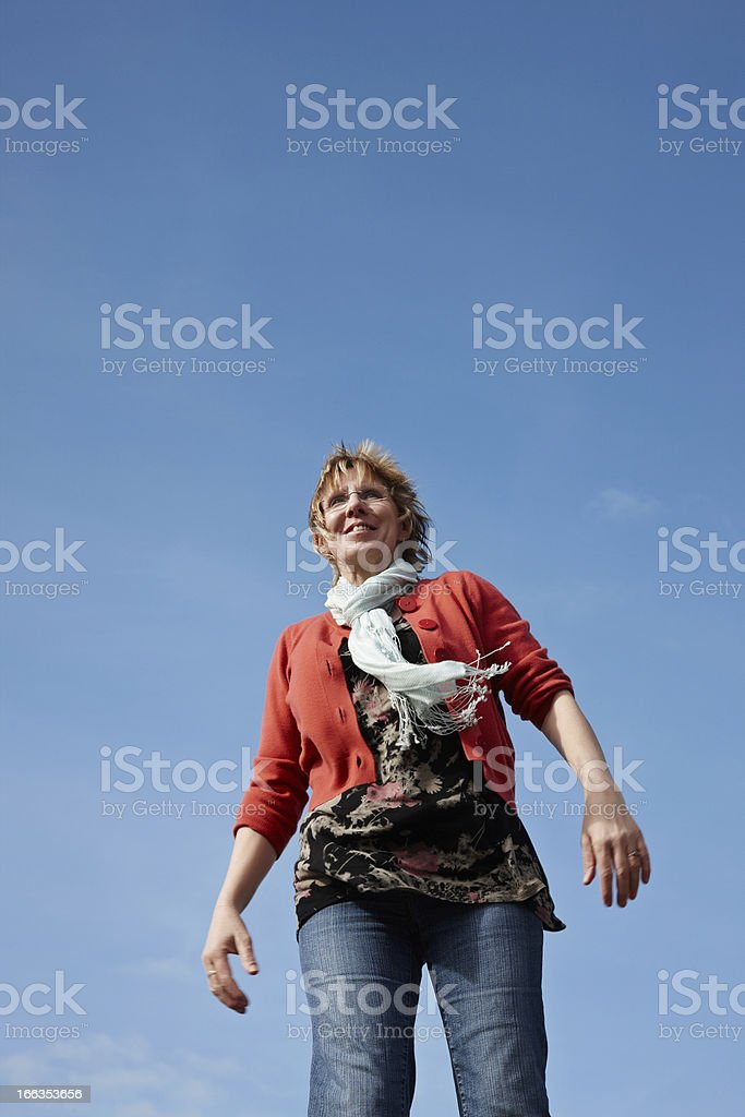 Mature blonde woman with blue sky background royalty-free stock photo
