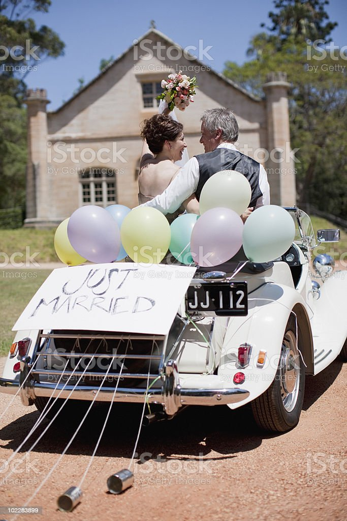 Mature bride and groom riding in convertible royalty-free stock photo