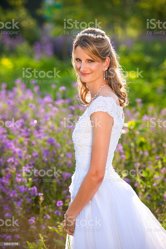Mature bride in field of purple flowers royalty-free stock photo