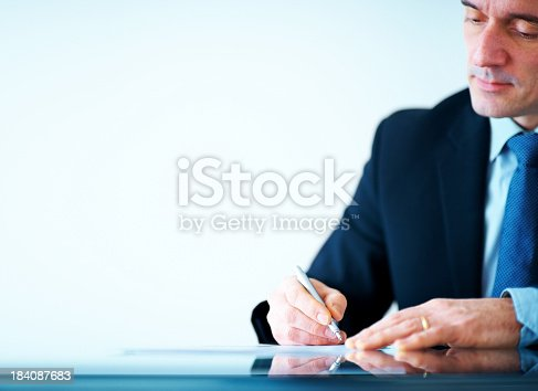istock Mature business executive writing on papers at office desk 184087683