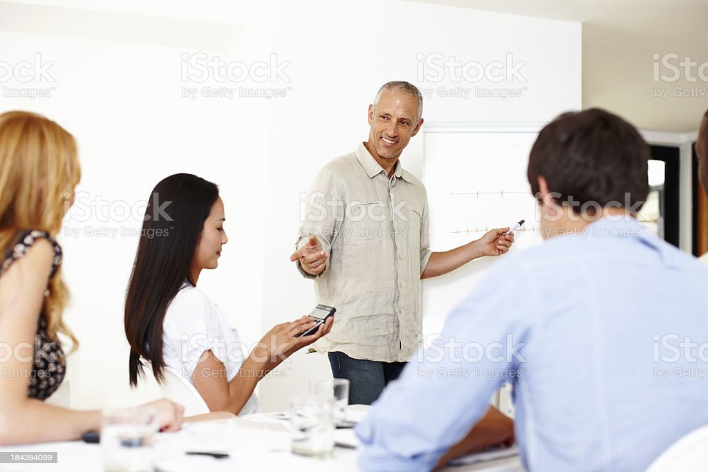 Mature business man presenting to colleagues royalty-free stock photo