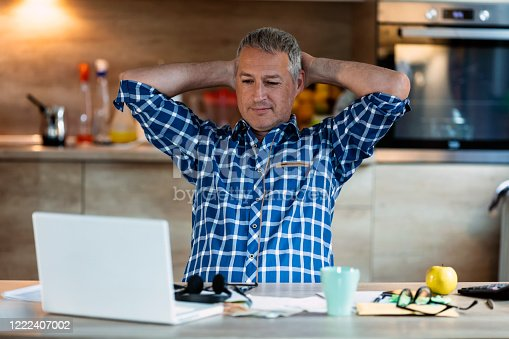 Smiling mature businessman holding hands behind head sitting at home office desk behind laptop. Happy Gray haired employee feeling no stress, relaxing, watching funny video after successful working.