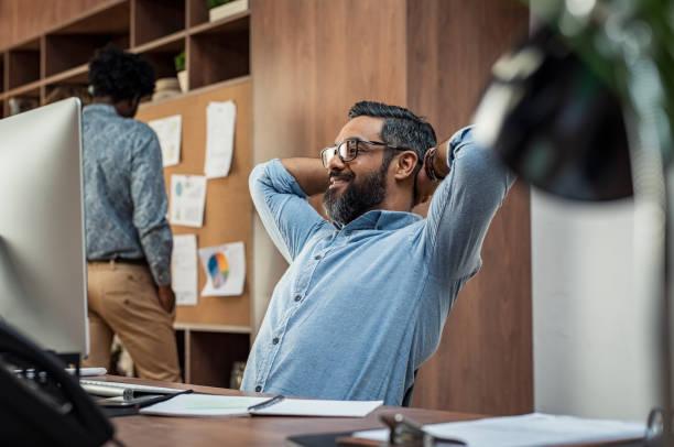 mature business man relaxing at work - mani dietro la testa foto e immagini stock