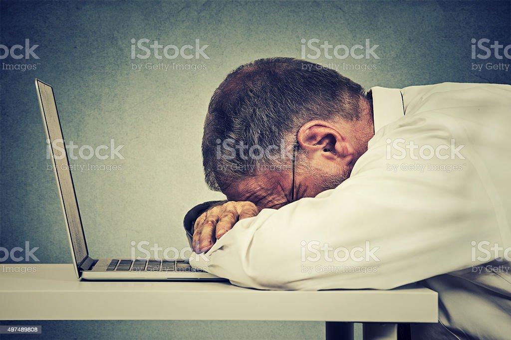 mature business man sleeping on a laptop stock photo