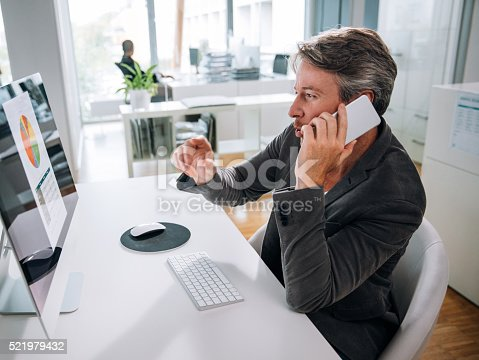 513583458 istock photo Mature business man talking on smartphone at desk 521979432