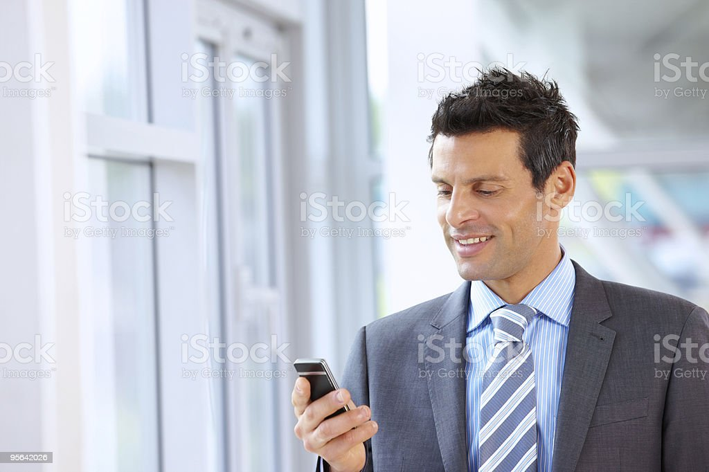 mature Business man texting on cellphone in modern office royalty-free stock photo
