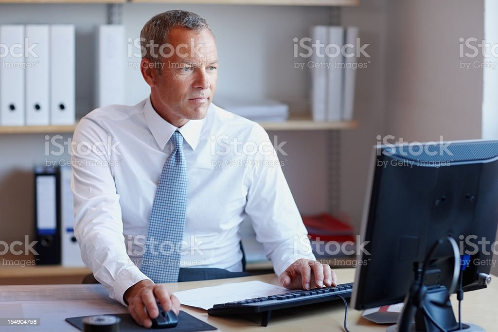 Mature business man using a computer in the office stock photo