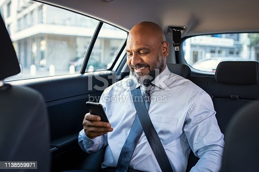 istock Mature business man using phone in car 1138559971