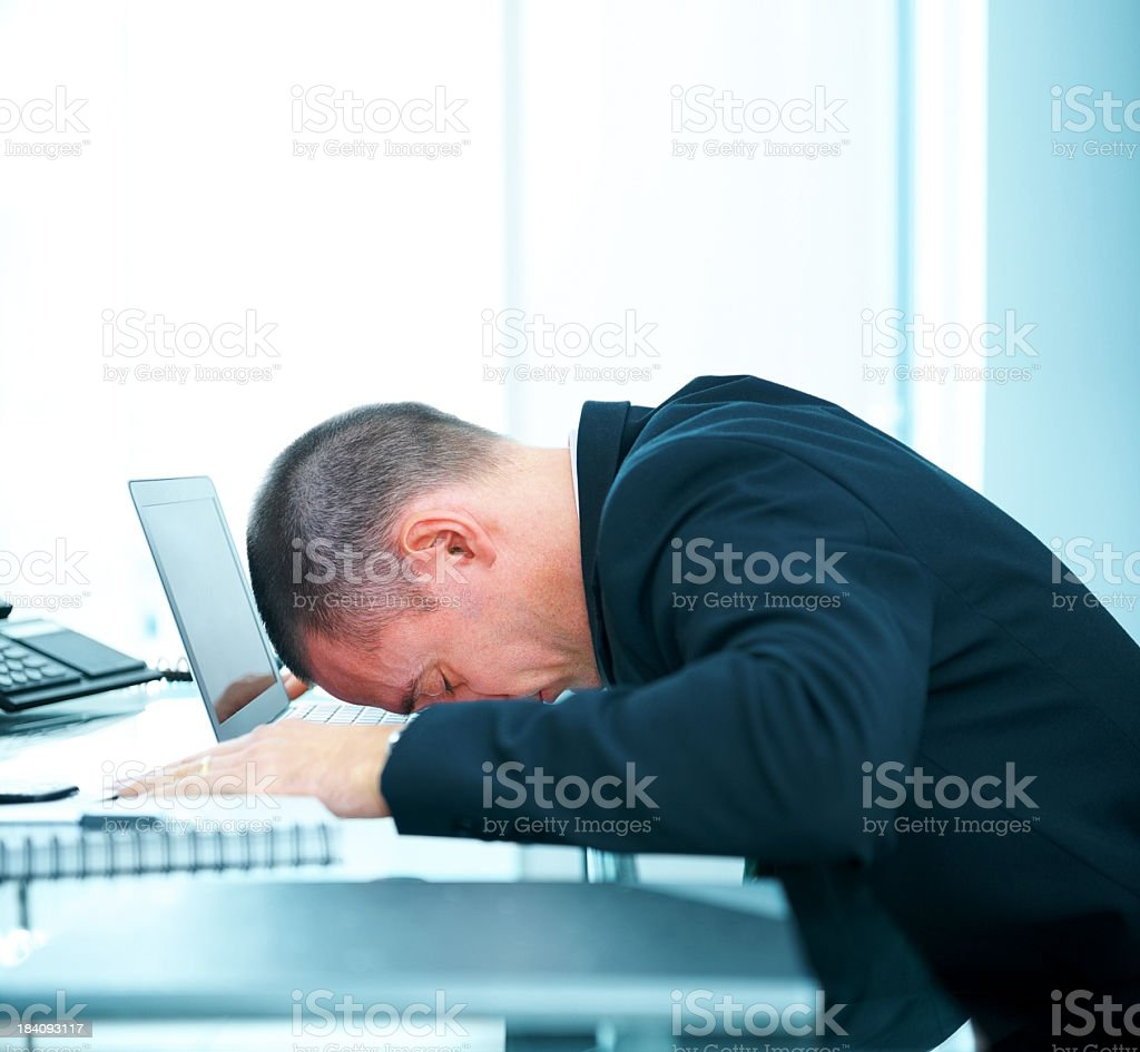 Mature business man with head laying on laptop royalty-free stock photo