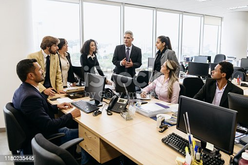 Team of business colleagues in office, listening to mature man in his 50s, gesturing and talking, serious expressions