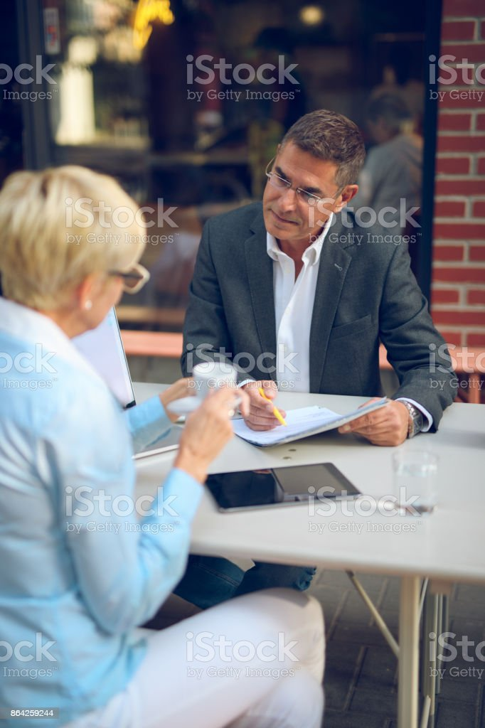 Mature business people collaborating after work royalty-free stock photo