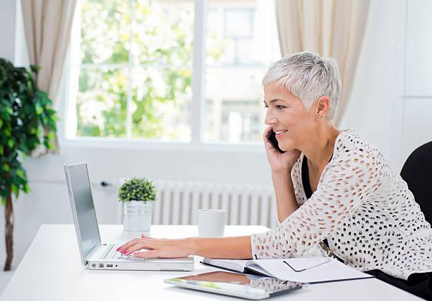 madura mulher de negócios no escritório - senior business woman tablet imagens e fotografias de stock