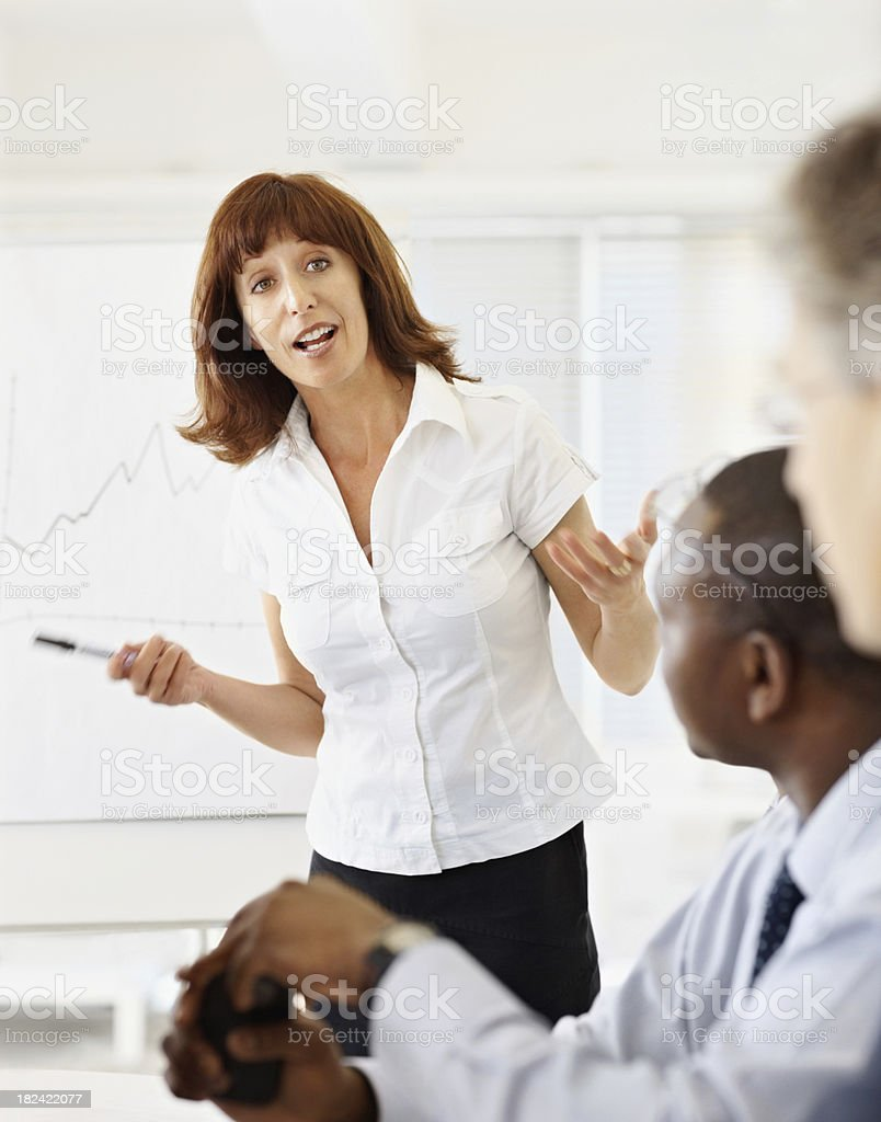 Mature business woman giving presentation to her associates royalty-free stock photo