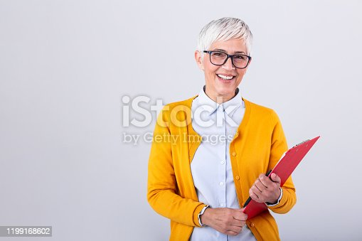 Mature business woman holding document on clipboard and glasses isolated on white background. Serious business woman looking at documents while holding her glasses in other hand