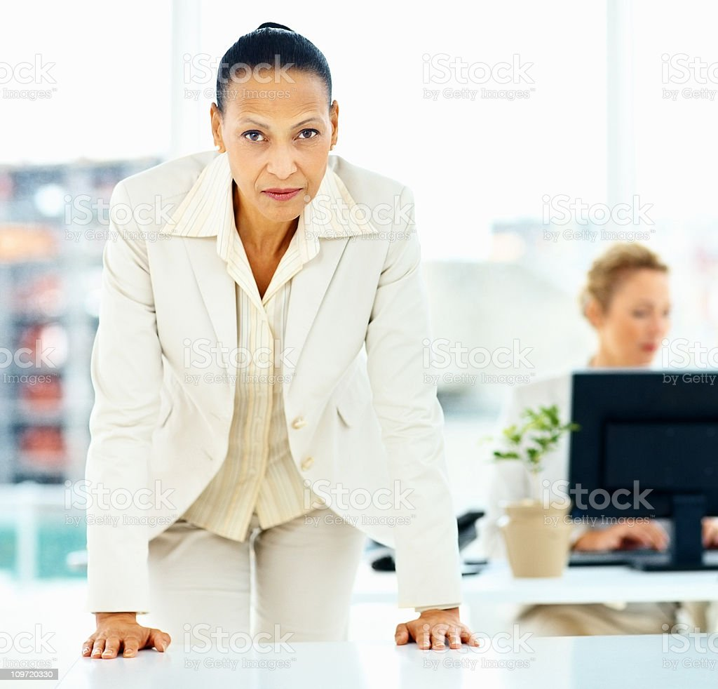 Mature business woman leaning over a table royalty-free stock photo