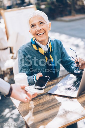 Mature business woman paying contactless with smartphone  outdoor at cafe