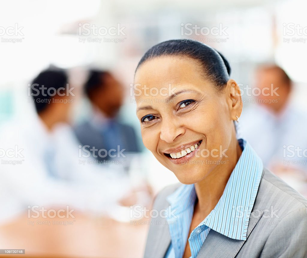 Mature business woman smiling with coleagues at the back royalty-free stock photo