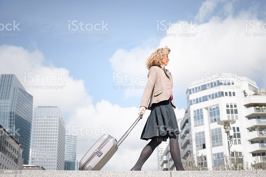 Mature Business Woman Walking in Business District with Wheeled Case royalty-free stock photo