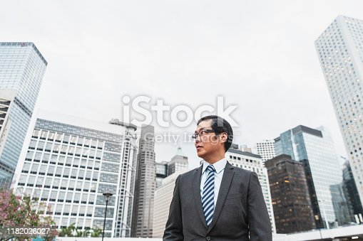 Chinese business professional in his 50s looking around in Hong Kong business district, commerce, architecture, finance