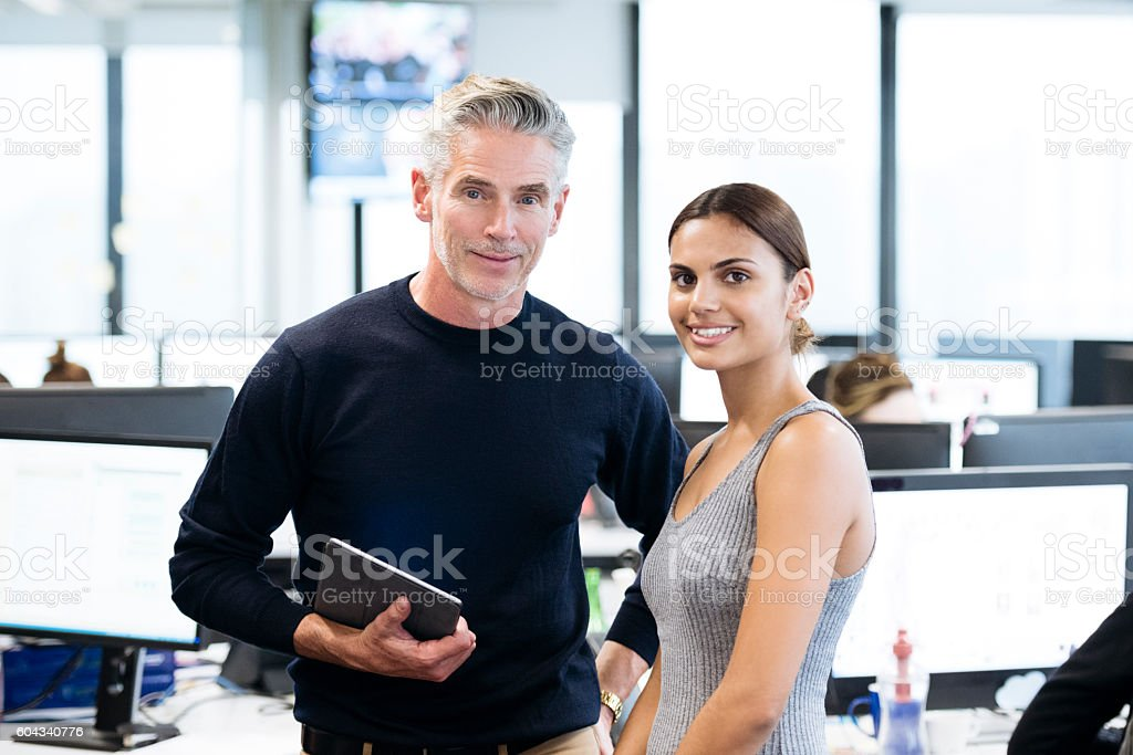 Mature businessman and young Aboriginal Australian woman in office stock photo
