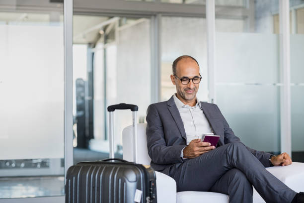 mature businessman at airport - airport stock photos and pictures