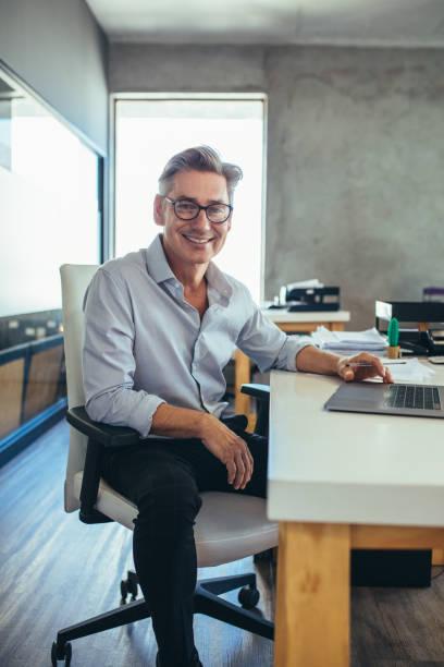 Reifer Geschäftsmann am Schreibtisch – Foto