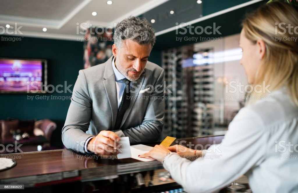 Mature businessman at hotel reception. stock photo