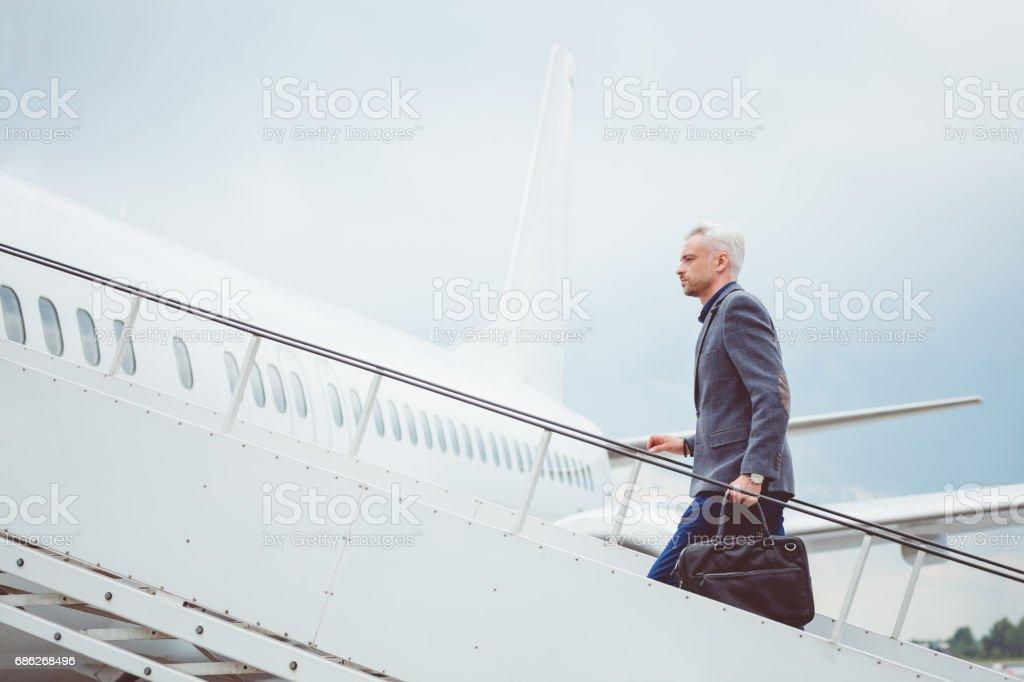 Mature businessman boarding airplane stock photo
