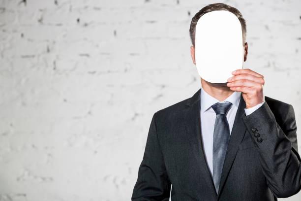 Hombre maduro que cubre cara con papel en blanco contra pared de ladrillo blanco en la oficina - foto de stock