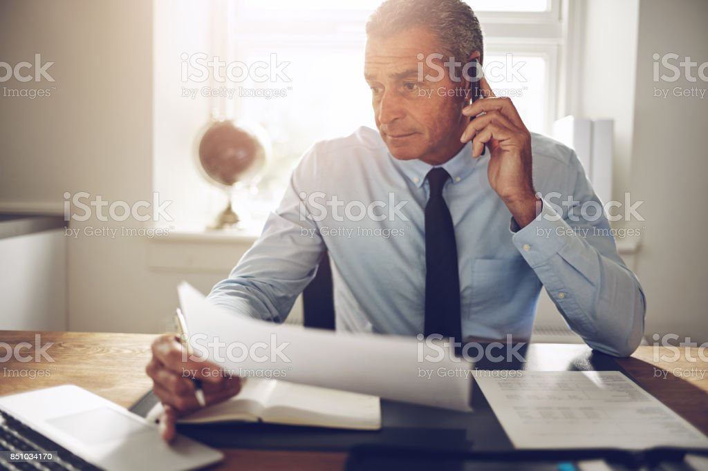 Mature businessman discussing paperwork over the phone in his office stock photo