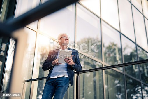 Mature businessman doing work on tablet outside of an office building.