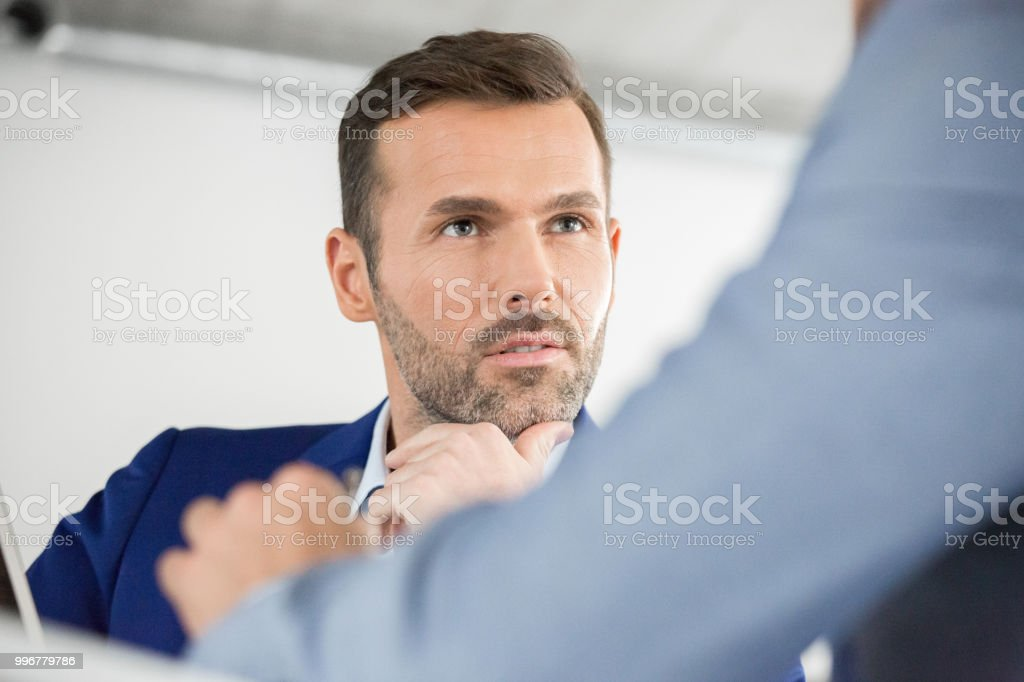 Mature businessman during meeting in office Mature businessman listening to colleague in a meeting. Businessmen in discussion during meeting. Adult Stock Photo