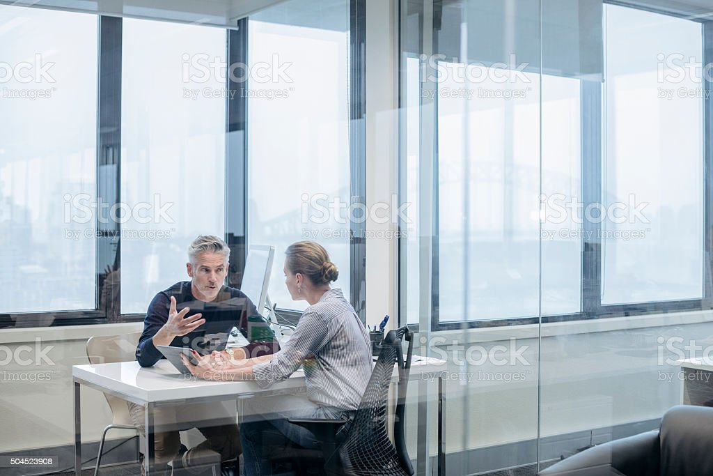 Mature businessman explaining to business colleague in office stock photo