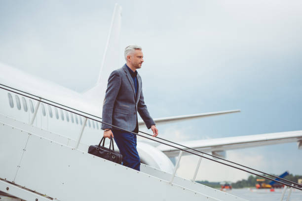 Mature businessman getting out of airplane stock photo