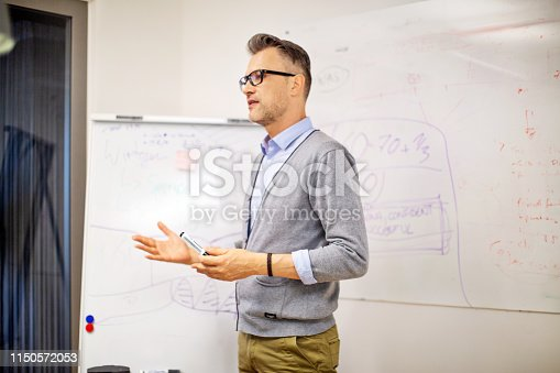 Mature businessman giving presentation in board room. Mid adult man sharing his ideas in  meeting at office.